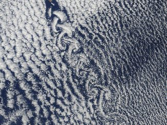 Scientific illustration: A satellite photo of clouds swirling into spirals.